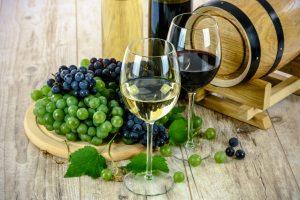 Wijnglazen met rode en witte wijn bij wijnvat en druiven